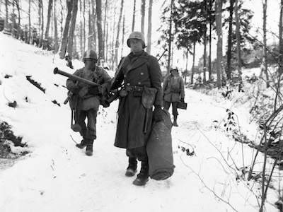 American engineers emerge from the woods and move out of defensive positions after fighting in the vicinity of Bastogne, Belgium.