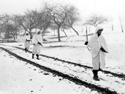 Three members, of an American patrol, Sgt. James Storey, of Newman, Ga., Pvt. Frank A. Fox, of Wilmington, Del., and Cpl. Dennis Lavanoha, of Harrisville, N.Y., cross a snow-covered Luxembourg field on a scouting mission in Lellig, Luxembourg, Dec. 30, 1944. White bedsheets camouflage them in the snow.
