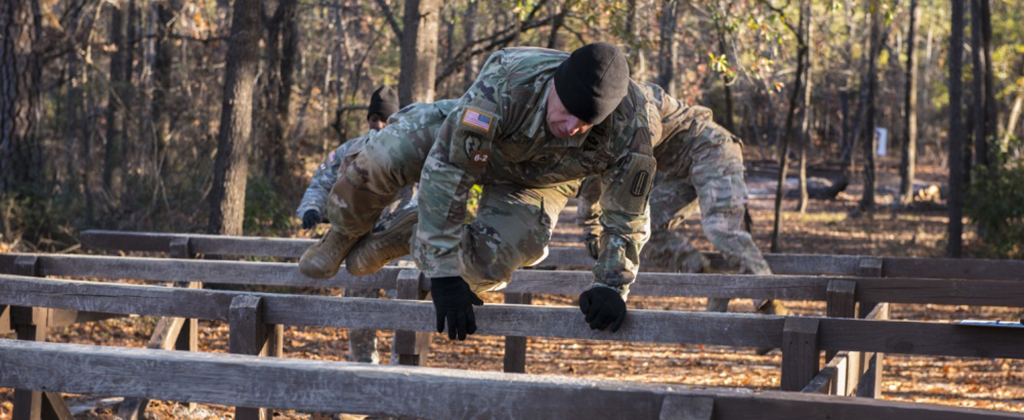 Soldiers leap over obstacles during training
