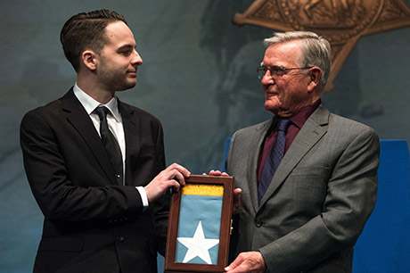 Mr. David L. Norquist, performing the duties of the U.S. deputy secretary of defense, presents the Medal of Honor Flag to U.S. Army Sgt. Travis Atkins' son, Trevor Oliver during a ceremony with Atkins' family at the Pentagon in Washington, D.C., March 28, 2019. The induction will add Atkins' name to the in the Hall of Heroes, the Department of Defense's permanent display of record for all recipients of the Medal of Honor. (DoD photo by U.S. Army Sgt. Amber I. Smith)