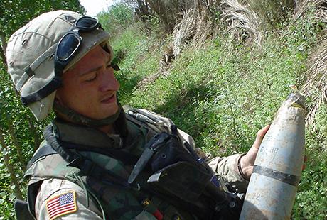 Staff Sgt. David Bellavia handles an improvised explosive device found on a patrol in Muqdadiyah Iraq, March 2004. (Photo courtesy of David Bellavia)