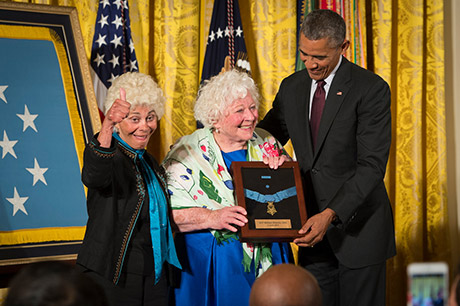 President Barack Obama bestows the Medal of Honor to Sgt. William Shemin, accepting on his behalf are his daughters, Elsie Shemin-Roth (middle) and Ina Bass (left), in the East Room of the White House, June 2, 2015. Shemin, a Jewish-American, distinguished himself as a member of 2nd Battalion, 47th Infantry Regiment, 4th Infantry Division, American Expeditionary Forces, during combat operations against the enemy on the Vesle River, near Bazoches, France, during World War I. While serving as a rifleman from August 7-9, 1918, Shemin left the cover of his platoon's trench and crossed open space in full sight of the Germans, repeatedly exposing himself to heavy machine gun and rifle fire to rescue the wounded. After officers and senior noncommissioned officers had become casualties, Shemin took command of the platoon and displayed great initiative under fire, until he was wounded, Aug. 9. Shemin was wounded by shrapnel and a machine-gun bullet that pierced his helmet that was lodged behind his left ear, leaving him partially deaf.  U.S. Army photo by Staff Sgt. Bernardo Fuller