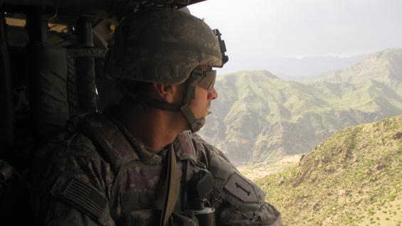 Capt. William Swenson looks out at the rough terrain of Eastern Afghanistan from a Black Hawk helicopter.