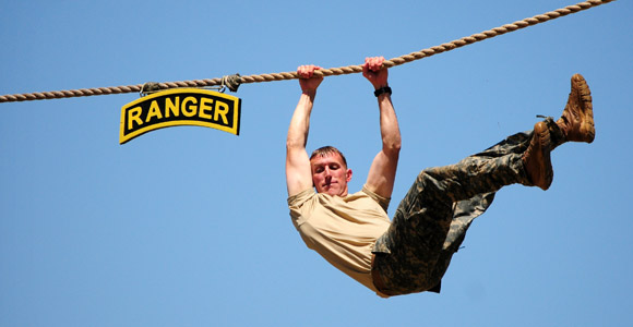 Soldier crossing overhead on a rope