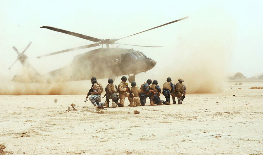 Commandos and Tactical Security Unit personnel watch UH-60 Black Hawk