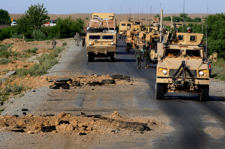 A convoy makes it's way around gigantic IED blast holes