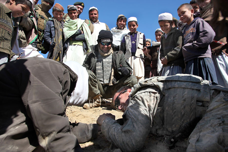 A Soldier takes a break to arm wrestle an Afghan man