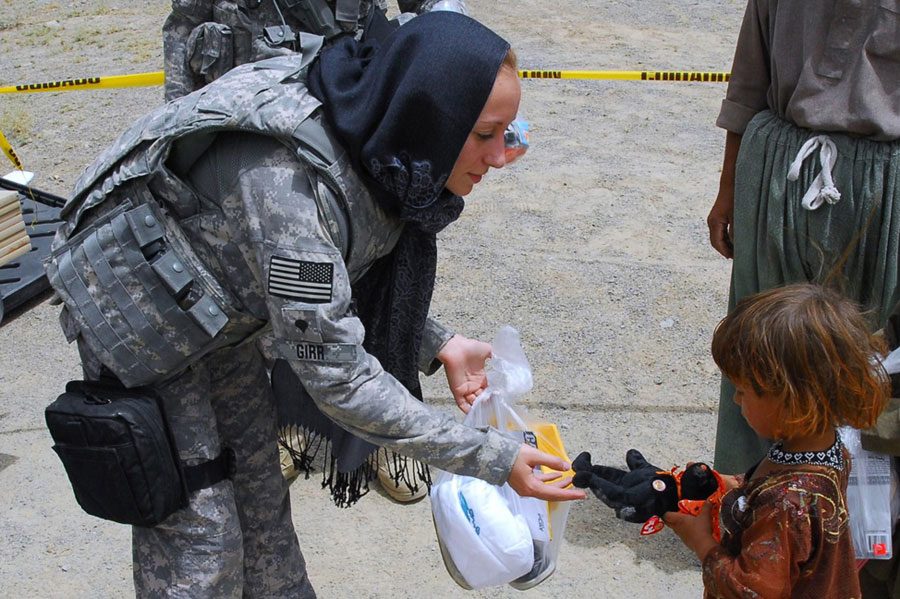 Soldier hands stuffed bear to young Afghan girl during humanitarian assistance mission