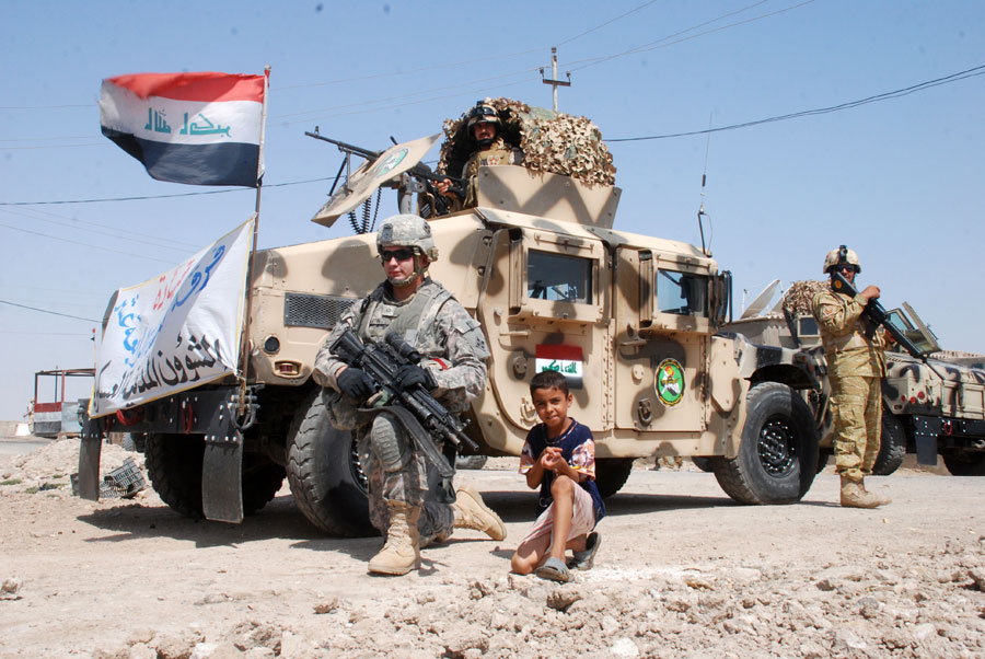 Soldier poses with boy in front of Humvee