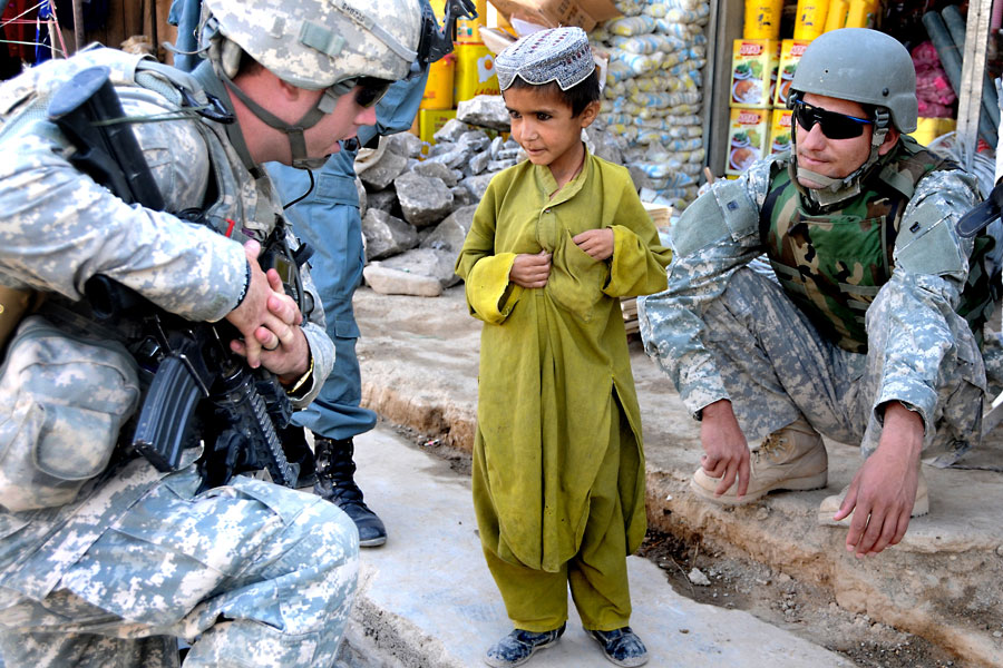 Afghan National Interpreter and Soldier from White Tank talk with Afghan boy during a patrol at a bazaar