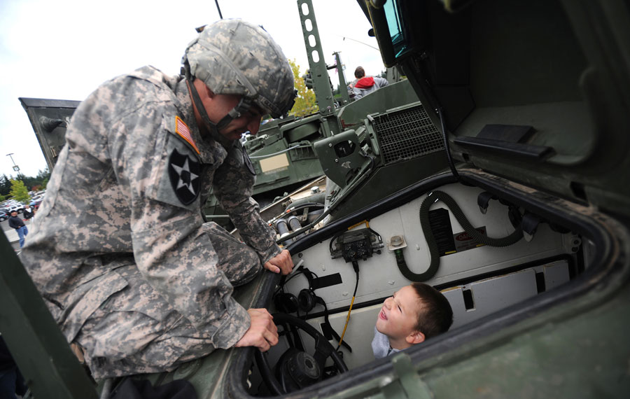 Soldier showing child Stryker combat vehicle