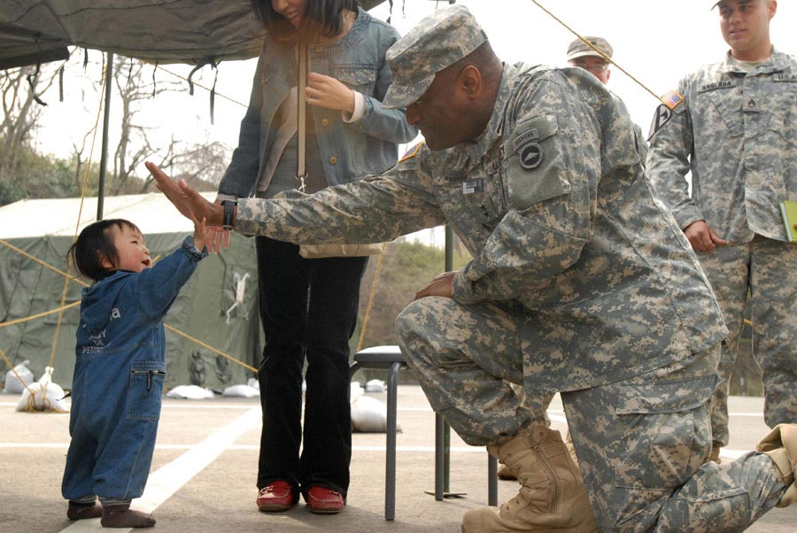 Major General Michael T. Harrison high fives a toddler displaced by the Great East Earthquake in Matsushima, Japan