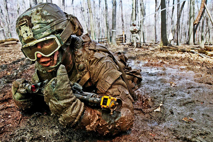 Crawling through mud, Private Charles Shidler searches for the next covered fighting position during individual movement techniques training