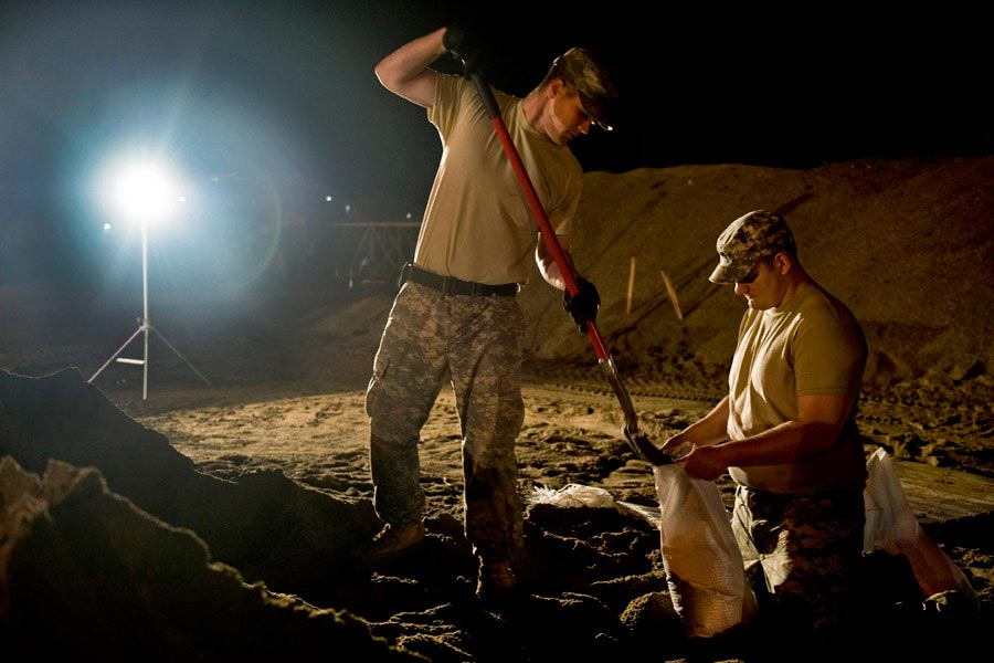 Specialist Benjamin Sukys and Specialist Robert Thorp work through the night filling sandbags