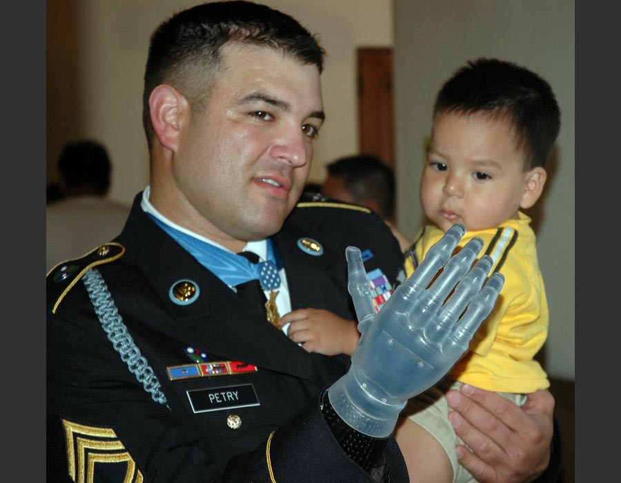 Sergeant First Class Leroy A. Petry, Medal of Honor recipient, 75th Ranger Regiment, poses for a picture with a friend's child after his welcome home parade in Santa Fe, New Mexico