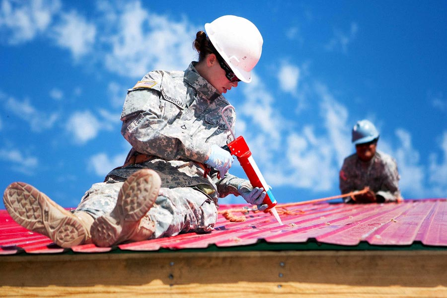 Private First Class Danielle Robinson seals gaps in sheet metal roofing during the Engineering Civic Action Program portion of Exercise Khaan Quest