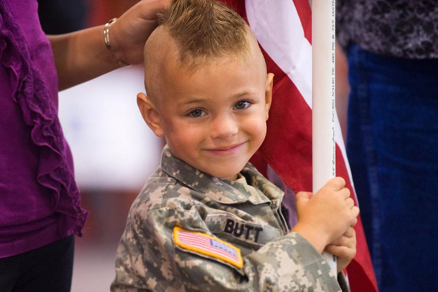 Gunner Butt, son of Sergeant First Class Walter Butt, stands with his family waiting for the return of their deployed Soldier