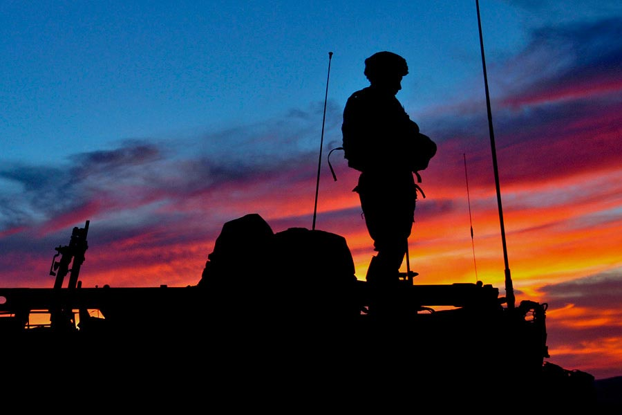 Soldier standing on Styker armored fighting vehicle at sunset