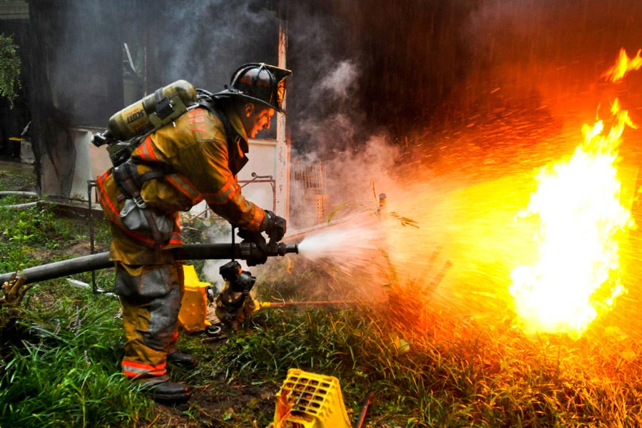 Private First Class Lucas Ternell, a volunteer firefighter, puts out a small debris fire in the yard of a house fire in Salisbury, Maryland