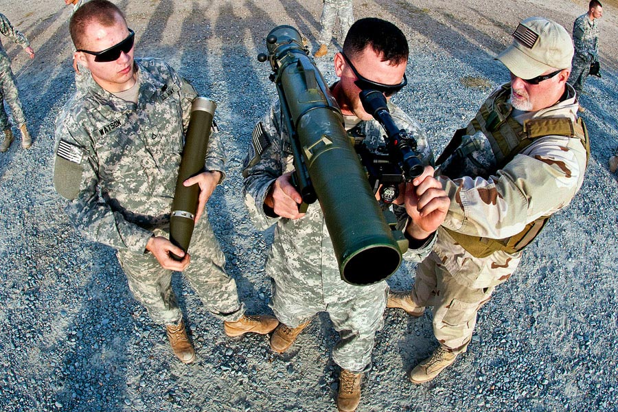 A civilian instructor coaches two paratroopers how to use a Carl Gustav 84 millimeter recoilless rifle