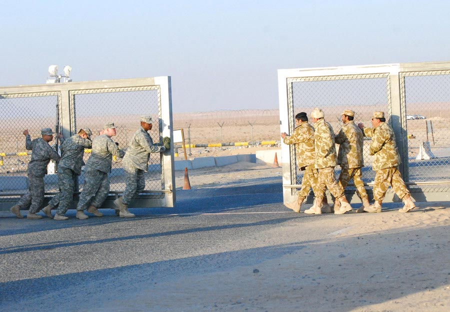 Kuwait border military police and Soldiers from the 265th Movement Control Team close the gate at the Khabari Crossing