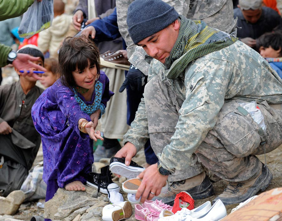 Sergeant First Class Manuel Delarosa finds shoes for a young Afghan girl