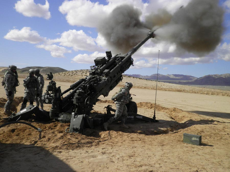 Soldiers firing a 155mm howitzer cannon