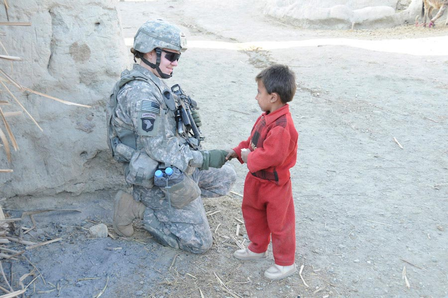 United States Army Soldier saying hello to Afghan child