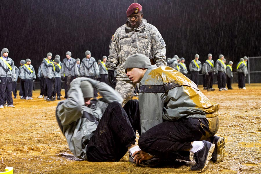 Sergeant First Class Eric Lloyd grades sit-up event of an Army Physical Fitness Test