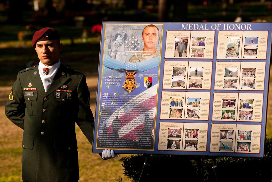 Soldier holds a poster depicting Staff Sergeant Robert Miller's life and Medal of Honor citation