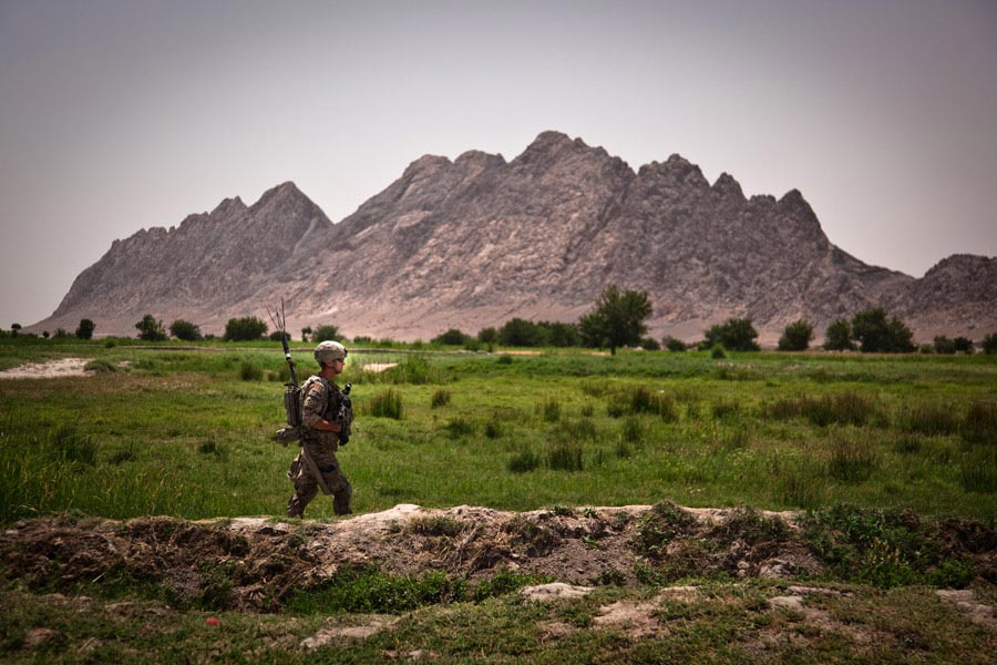 A Soldier walks through a valley during a patrol through Malajat, Afghanistan
