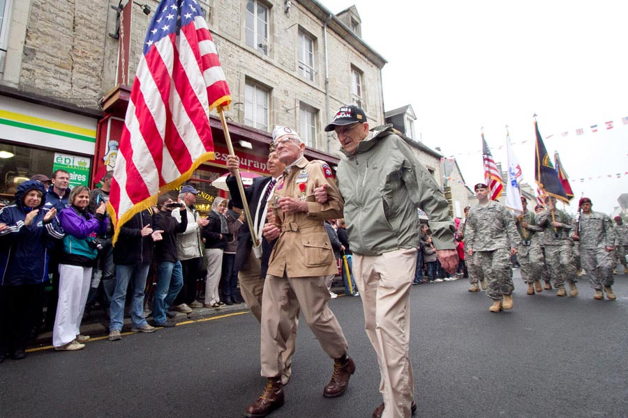 Zane Schlemmer, a veteran United States Army paratrooper who jumped into northern France as a sergeant with the 82nd Airborne Division, walks in his jump boots down the main street of Sainte-Mère-Église with other World War II veterans during the 67th anniversary of the Allied invasion of France
