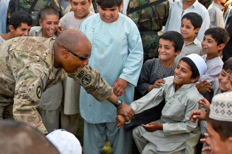Captain Derrick W. Dew plays with young residents of Kandahar City during a ribbon cutting ceremony for a new soccer field