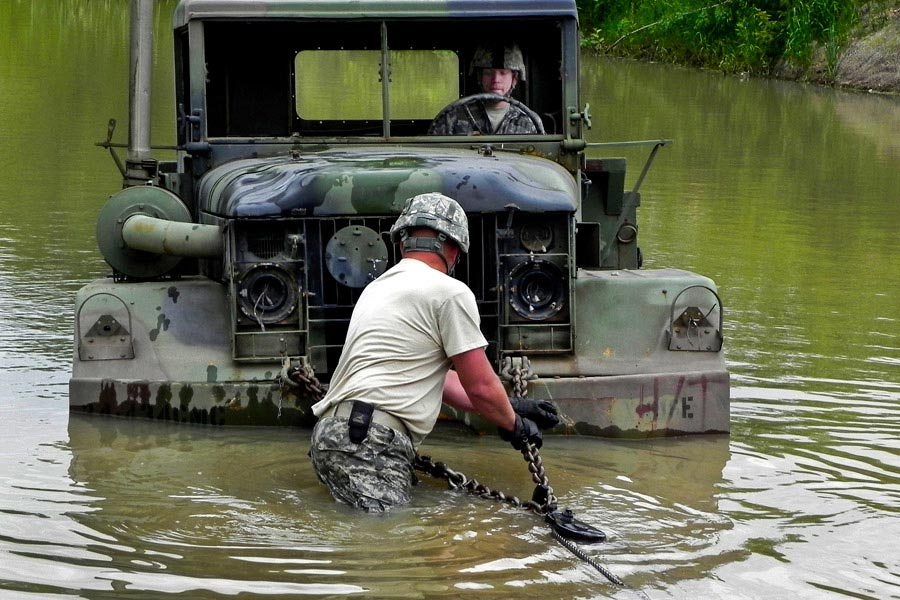 Staff Sergeant Keith Ericson checks the cable connection of a vehicle stranded in water during a training exercise while Specailist Andrew Miller steers the vehicle