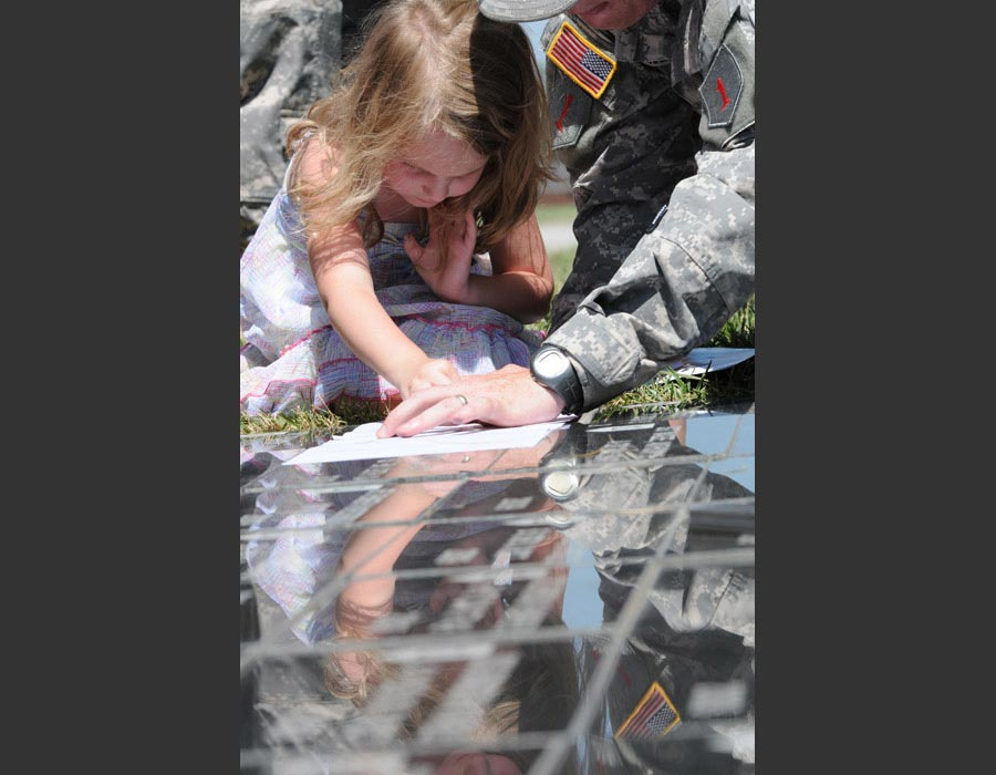 Hannah Maher makes a rubbing of the memorial stone honoring her dad, Sergeant Brent Maher, following the Victory Park Ceremony at Fort Riley, Kansas