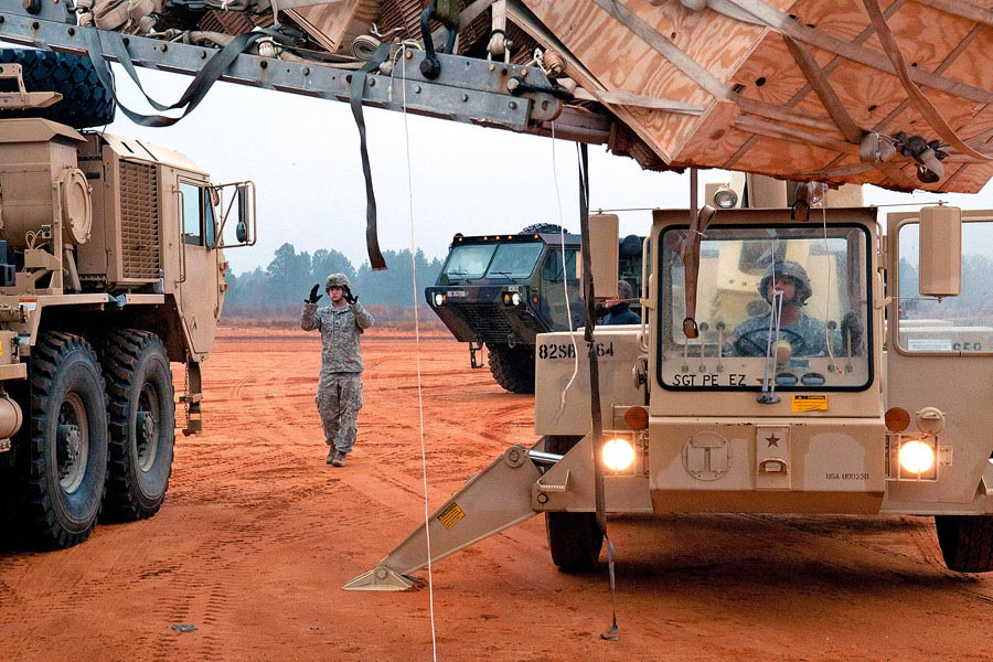Specialist Jordan Tackett directs a Heavy Expanded Mobility Tactical Truck into place for a crane operator at Camp MacKall, North Carolina