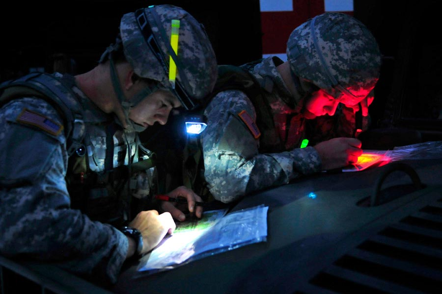 Captain Nick Franck, left, and Second Lieutenant Charles Smith plot their points on maps for the day-to-night land navigation course during the United States Army Europe Best Junior Officer Competition