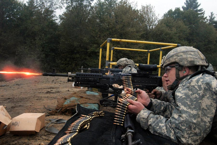 Private Stephen Justice acts as an assistant gunner and feeds rounds through a M240B machine gun