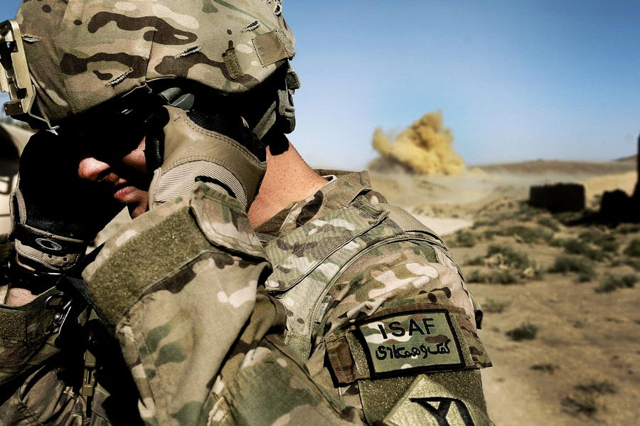 Private First Class Richard Mills secures his eyes and ears as Afghan National Army Soldiers conduct a controlled detonation