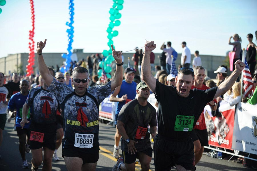 Major General David L. Mann (right) holds the hand of Captain Ivan Castro, a blind runner, while they approach the finish line at the 2011 Army Ten-Miler