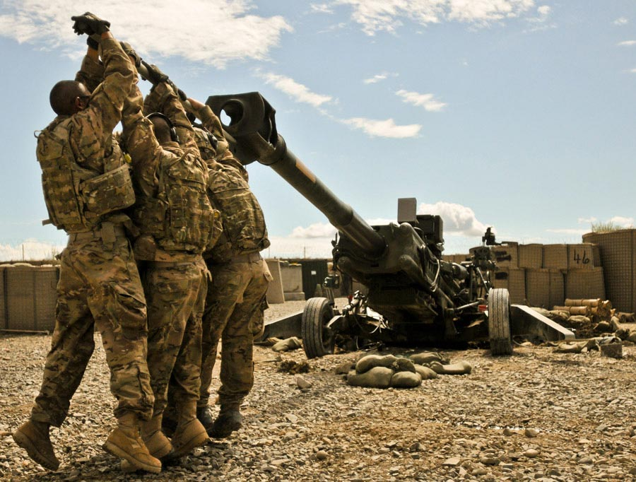 Soldiers work at dislodging their M-777 155mm howitzer from the three-foot deep hole it dug its spades into after firing several rocket-assisted projectiles