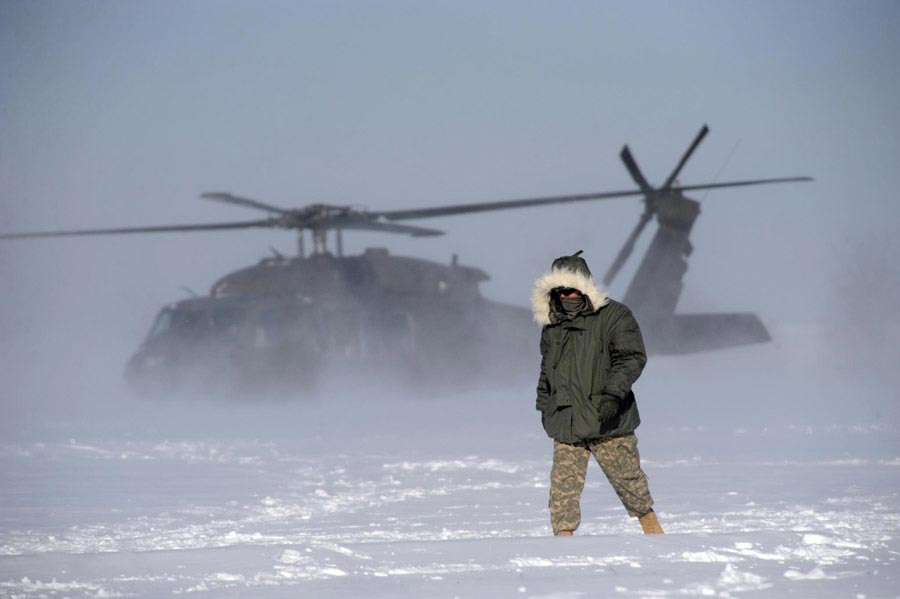A Soldier oversees the liftoff of a UH-60 Black Hawk flown during medical evacuation training in harsh weather conditions