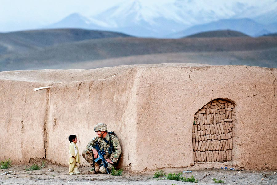 Sergeant Joshua Smith, with 82nd Airborne Division, chats with an Afghan boy