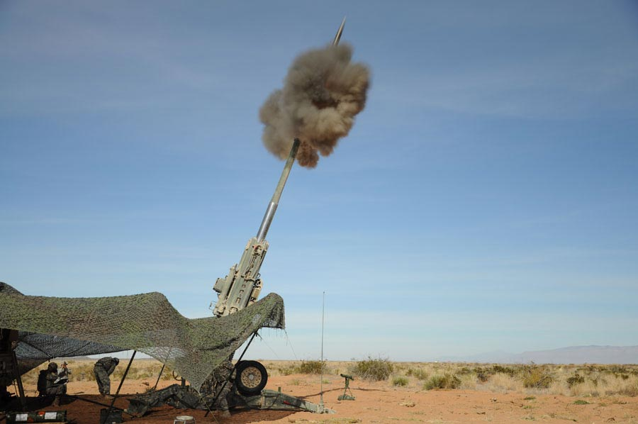 M982 Excalibur 155mm round leaves barrel of an M777 Howitzer during live-fire shoot