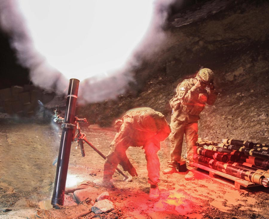 Specialist Jerel Martinez (near right) and Private First Class Andrew Bemis, indirect fire infantrymen assigned to 101st Airborne Division (Air Assault), fire 120mm mortar during night-fire