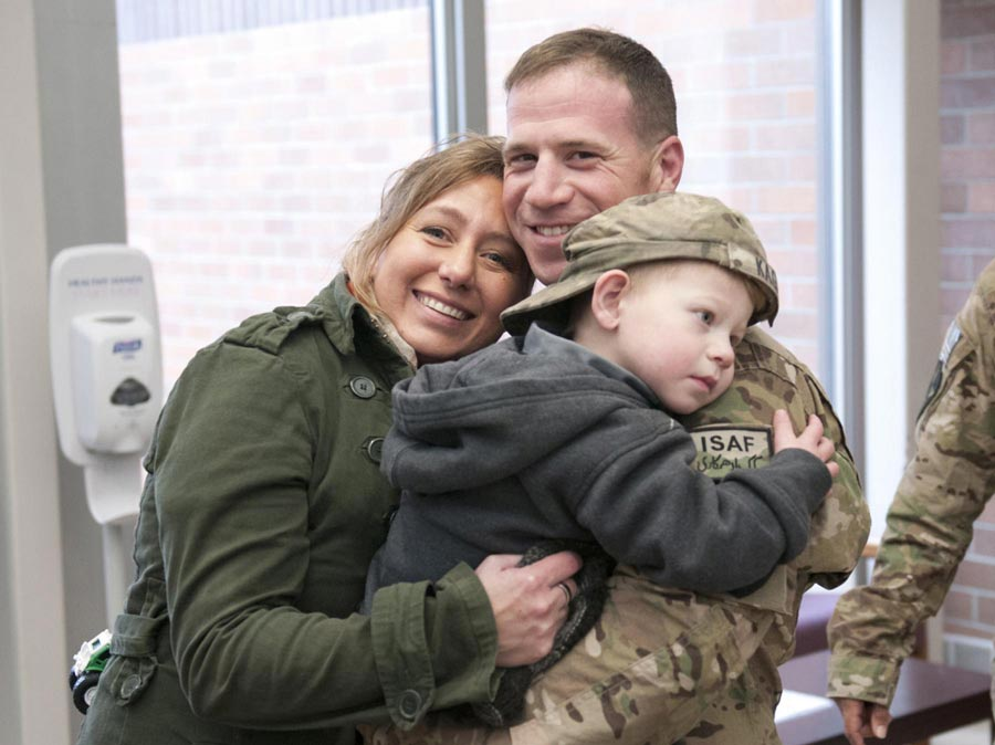 Valerie Kagan and her son Sean, hold tightly to their returning 2nd Infantry Division Soldier, Sergeant First Class Jeremy Kagan, after welcome-home ceremony