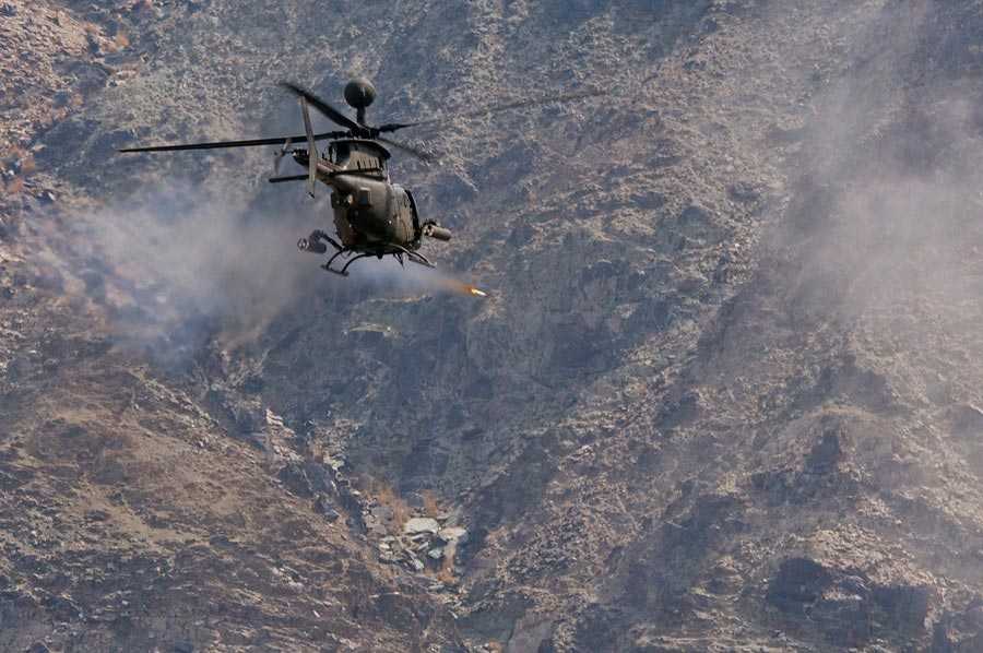 OH-58D Kiowa Warrior from 82nd Combat Aviation Brigade, fires 2.75-inch rocket at mountainside