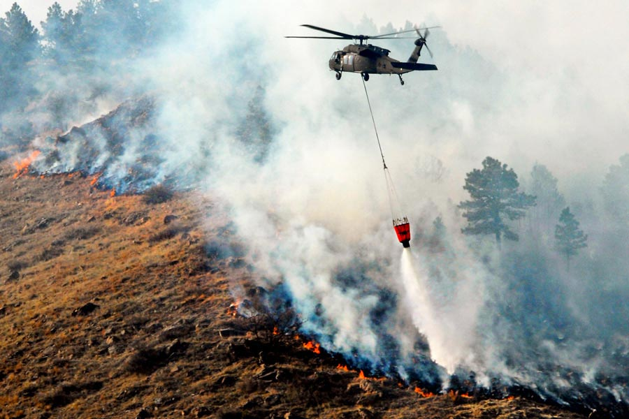 South Dakota Army National Guard UH-60 Black Hawk helicopter drops 600 gallons of water on fire