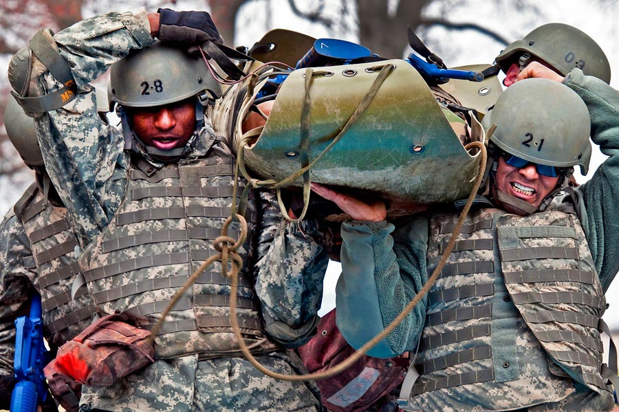 Four members of 316th Sustainment Command (Expeditionary) carry simulated casualty through an obstacle on a SKED litter