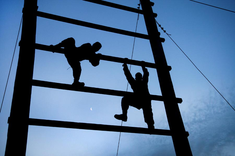 Soldiers from United States Army Reserve Command headquarters climb an obstacle